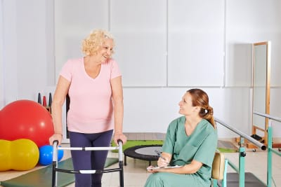 elderly women with walker in physical therapy in nursing home
