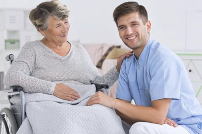 senior woman on a wheelchair and smiling male caregiver