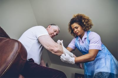 caregiver putting a bandage on a senior man's arm in his home